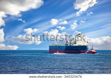 Tanker ship with escorting tugs leaving port. - stock photo