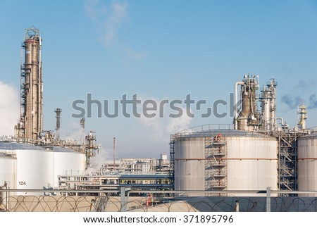 tanks in front of an oil refinery with smoking chimneys against blue sky - stock photo