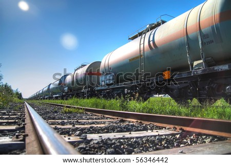 Tanks with fuel being transported by rail, taken in backlit - stock photo