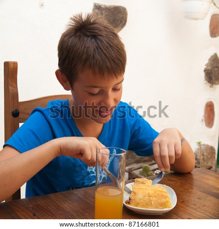 tanned caucasian boy eating a portion of tortilla in a cafe - stock photo