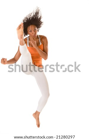 Tanned fit sporty female jumps in air and kicks (motion blur) - stock photo