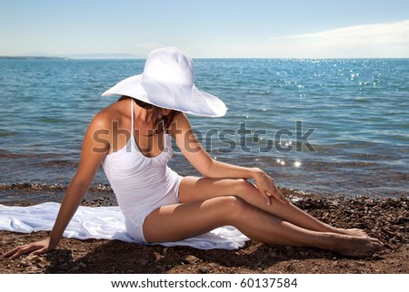 Tanned girl in a white dress and white hat on the beach