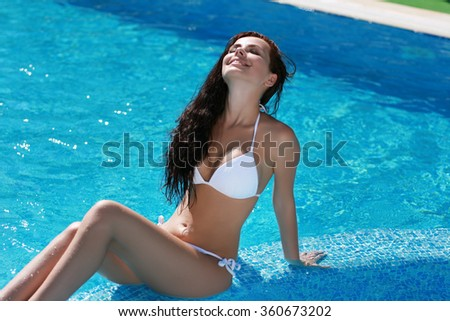 Tanned girl in  white bathing suit in pool - stock photo