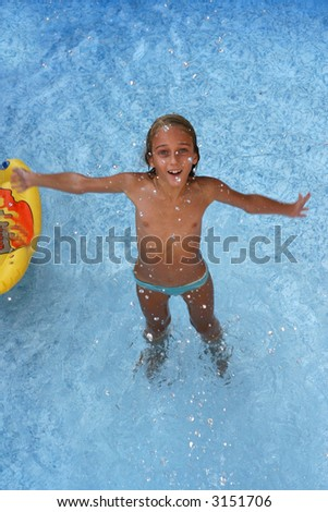 Tanned girl standing in the water and smiling