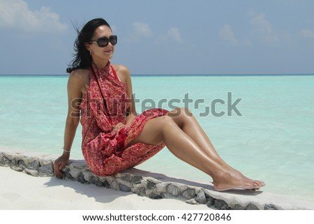 Tanned girl with dark hair in red pareo in the Maldivian beach - stock photo