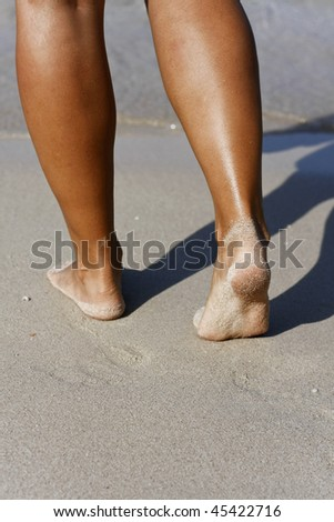 Tanned legs on sandy beach - stock photo