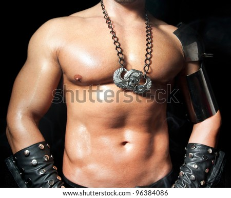 Tanned muscular male torso on a black background - stock photo
