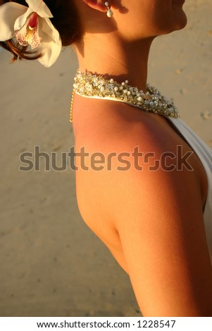 Tanned sexy bride on beach with white dress, necklace and flower - stock photo
