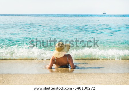 Tanned tourist woman in swimsuit and hat lying on sand and enjoying clear blue waters of Mediterranean sea at Cleopatra beach, Alanya, Mediterranean region, Turkey