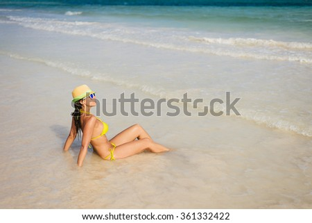 Tanned woman in yellow bikini enjoying relax bath at seashore on beach vacation. Brunette girl tanning and relaxing on summertime. - stock photo