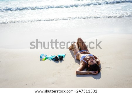 Tanned woman on tropical beach vacation resting after snorkeling. Brunette beautiful girl in white bikini relaxing and sunbathing. - stock photo