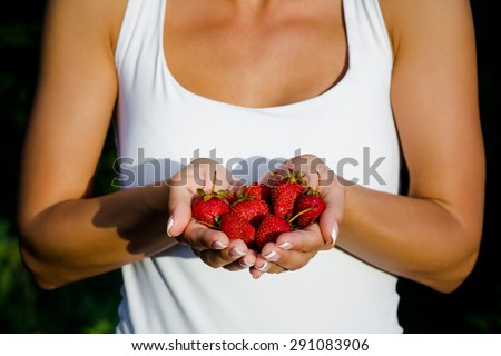 Tanned woman presenting cherries in her hands. Girl in white singlet keeping red cherries in front of her.