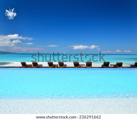 Tanning beds beside luxury infinity swimming pool at tropical beach - stock photo