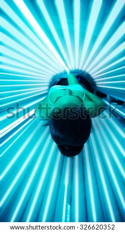 Tanning in bed solarium, young woman lying in bed solarium  - stock photo