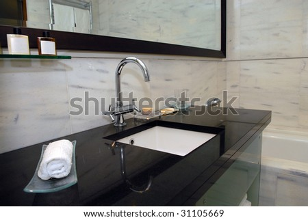 Tap and a sink in a bathroom - stock photo