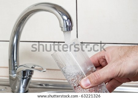Tap water and a glass of water - stock photo