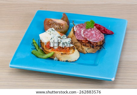 Tapas with cheese, salami fuet and grilled bread - stock photo