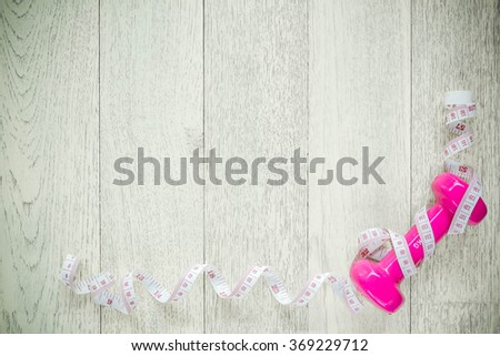 Tape and dumbbells fitness on wooden background. Different tools for sport - stock photo