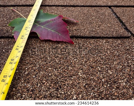 Tape measure and autumn leaf on asphalt shingles - stock photo
