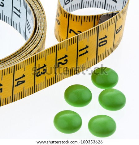tape measure and tablets, as a symbol for diet pills. remove - stock photo