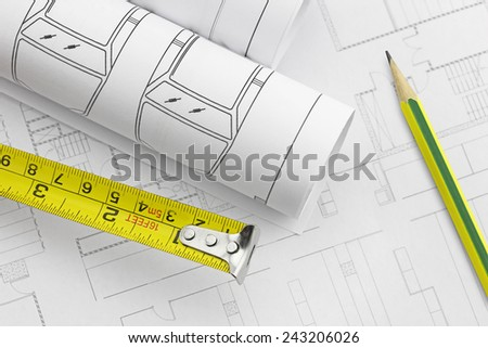 Tape measure and work tool, pencil over a construction plan drawing and architect rolls - stock photo