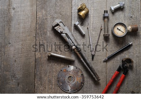 Tape-measure, blueprints, internal screws, bolts, manometer, diamond wheel, pliers, pipe wrench on old wooden table.  top view. copy space. - stock photo