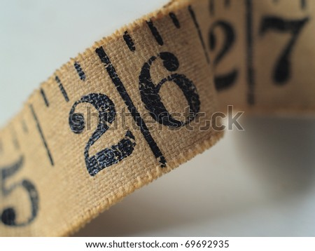 Tape Measure for sewing.  A close up of the number 26 is seen in the ripple of the cloth tape measure. - stock photo