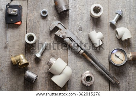 Tape-measure, internal screws, pipe wrench, pipe screw, PVC pipe connectors, manometer on old wooden table - stock photo