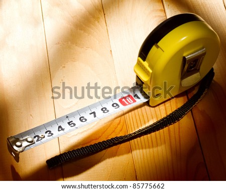 Tape measure isolated on wooden background - stock photo