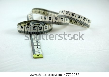 tape measure on a white surface - stock photo