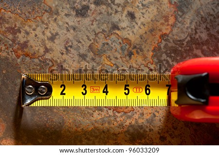 Tape measure on the rusty background - stock photo