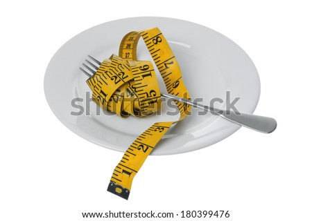 Tape measure with fork on plate - stock photo