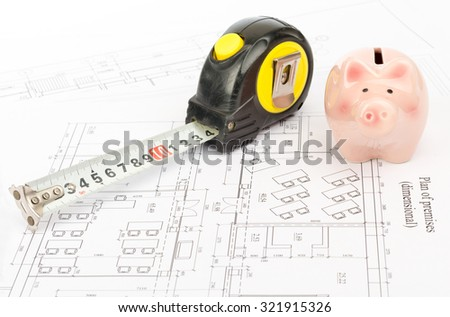 Tape measure with piggy bank on draft background - stock photo