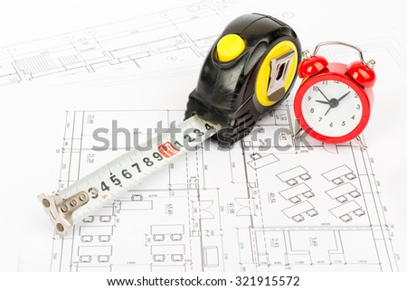 Tape measure with red alarm clock on draft background