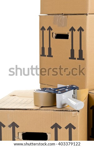 Tape roller on stack of moving carton boxes over white background - stock photo