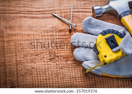 tapeline glove hammer nails on vintage wooden board with copyspace construction concept  - stock photo