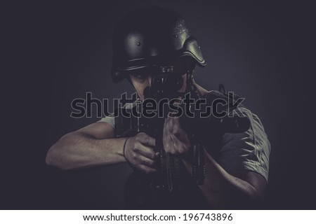 Targeting, paintball sport player wearing protective helmet aiming pistol ,black armor and machine gun - stock photo