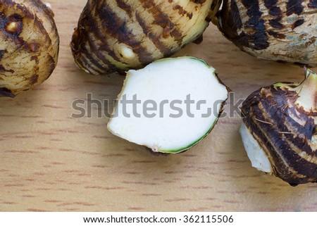 Taro on a wooden background,Cut white taro on wooden cutting board,Fresh taro on wooden background,Taro root on wooden background - stock photo