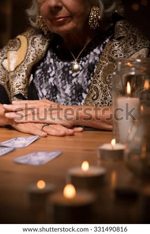 Tarot card reader in fortune telling salon - stock photo