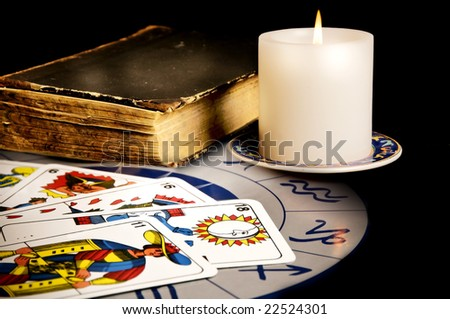 tarot cards with old book and burning candle - stock photo