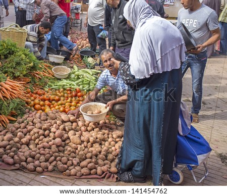 TAROUDANT, MOROCCO - OCTOBER 24: Woman buying fresh vegetables from the market on October 24, 2012 in the ancient town of Taroudant in Morocco. - stock photo
