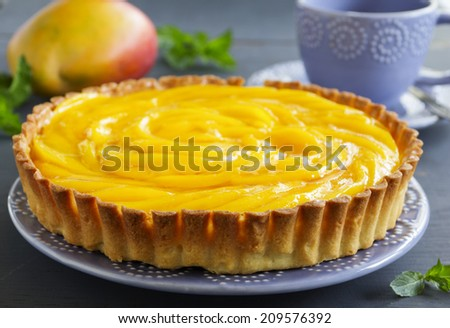 Tart with mango and stuffed with cream cheese. - stock photo