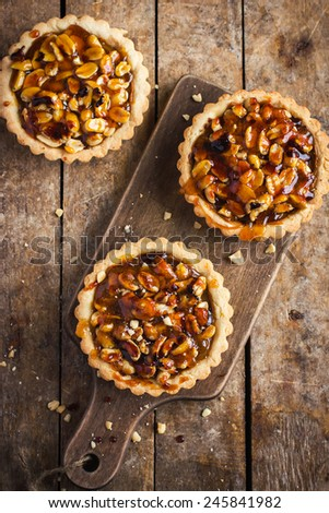 Tart with nuts and caramel on a rustic  background, top view - stock photo