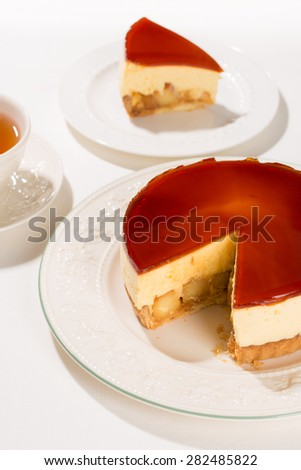 Tart with sauteed apples, topped with a thick layer of Chiboust cream, and iced with caramel jelly.  Chiboust cream is a custard lightened with Italian meringue. Shot in a sharp light. - stock photo
