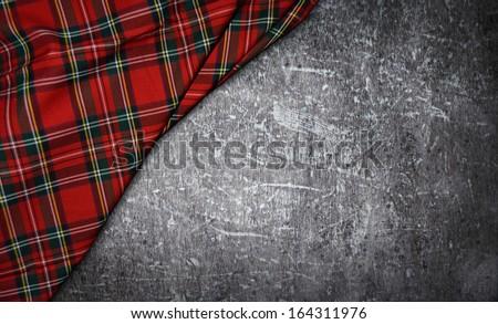 tartan textile on stone background - stock photo