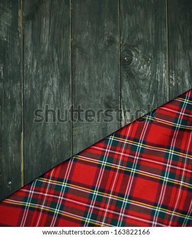 tartan textile on wooden background - stock photo