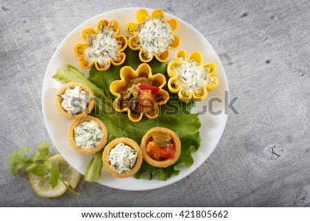 Tartlets filled with vegetables and cheese and dill salad on white plate and leaf against rustic wooden background, horizontal top view with copy space - stock photo
