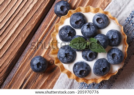 Tartlets with blueberries and cream cheese closeup on wooden background horizontal view from above   - stock photo
