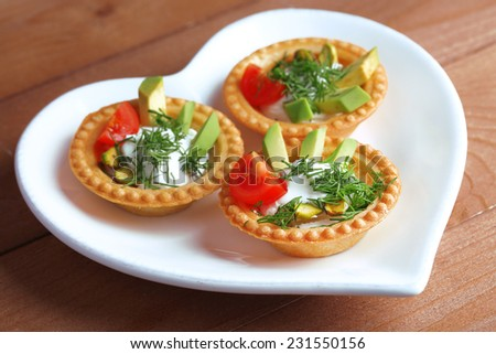 Tartlets with greens and vegetables with sauce on plate on table - stock photo