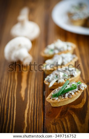 tartlets with mushroom stuffing on the wooden table - stock photo